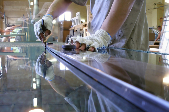 A glazier scribing a glass pane before cutting and silicone treating it